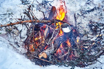Melting snow in a metal cooking utensil over a camp fire
