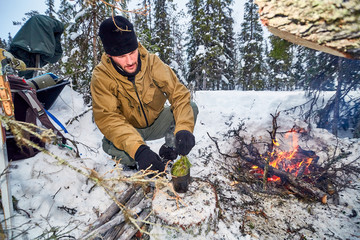 Man in military clothes prepares an infusion of pine shoots in a metal cooking utensil over a fire