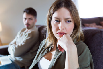Offended young woman ignoring her angry partner sitting behind her on the couch at home.