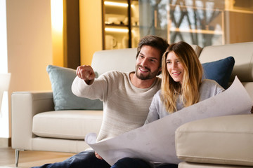 Portrait of a couple in love who is planning new home and furniture. The two couples smile and are happy with the futuristic project together. Concept of: future, family, design and projects.