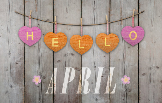 Hello April written on hanging pink and orange hearts and weathered wooden background, with flowers
