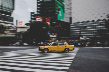 Taxi speeding across Shibuya crossing in Tokyo Japan