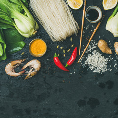 Asian cuisine ingredients over slate stone background, top view, square crop, copy space. Vegetables, spices, shrimp, rice, sauces for cooking vietnamese, thai or chinese food. Clean eating concept