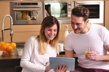 A couple in the kitchen looks at the tablet with the souvenir photos of their holidays or of the past times while having breakfast and smiling happily. Concept of: family, technology, memories