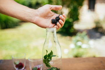 Placing Blackberry In Glass Bottle