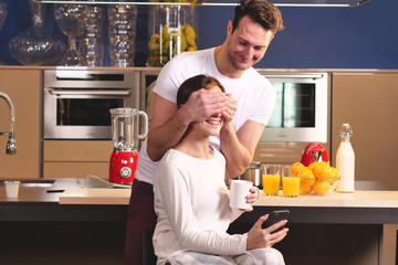 Young  husband covers his wife's eyes to make a surprise, while she was drinking a hot tea and looking at her phone