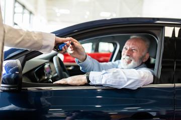 Happy man at car showroom buying a new car.