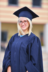 Portrait of a happy female student standing outside on her graduation day