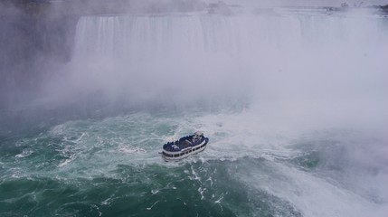 Boat with tourists enjoying the beautiful and impressive panorama of the Niagara Falls in Ontario (Canada) on a bright autumn day with water crashing down the falls onto rocks creating a lot of mist
