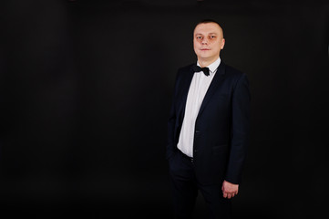 Stylish man in suit posed on studio isolated on black.
