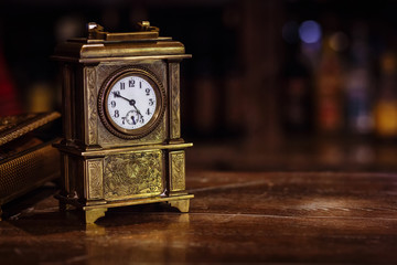 antique clock stand on a wooden table