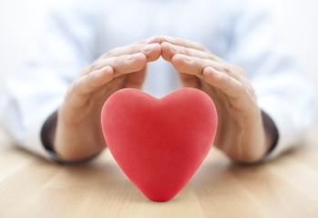 Red heart covered by hands. Health insurance or love concept