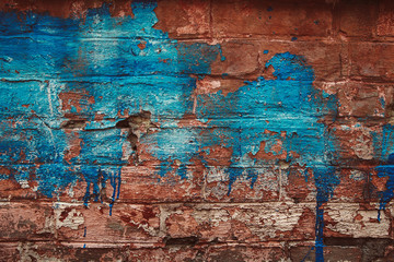 The old brick wall is faded with blue paint.