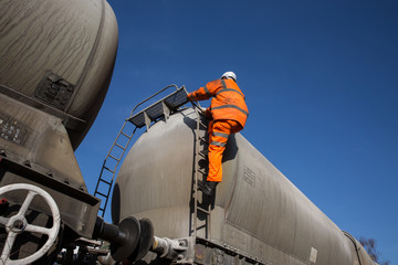 A Railway Worker wearing hi viz clothing and safety work wear climbing onto a Tanker Wagon at the track side.