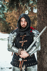 man knight with a sword near a tree