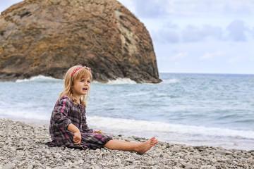 Happy little girl sitting along the ocean beach