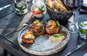 Grilled steak meat with foie gras, shrimp, cheese and glass of red wine