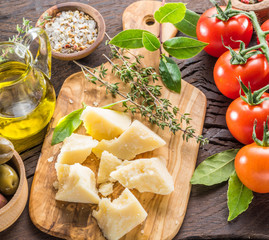 Parmesan cheese on wooden cutting board. Food background.