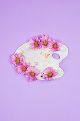White plastic artist palette with violet daisies in it. Creativity concept, spring/summer floral composition, flaltlay, violet background