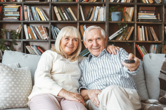Senior couple together at home retirement concept watching tv holding remote controller