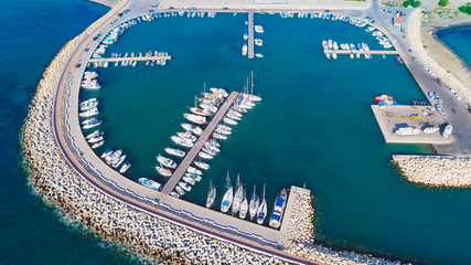 Aerial bird's eye view of Zygi fishing village port, Larnaca, Cyprus. The fish boats moored in the harbour with docked yachts and skyline of the town near Limassol from above.