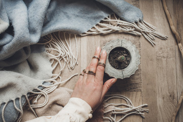 pastel colors female hand in vintage rings near pot with cactus on wool blue scarf which rests on a wooden background