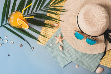 Beach accessories, a palm leaf and cocktail on a blue background.