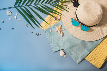 Beach accessories and a palm leaf on a blue background.