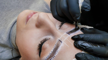 Permanent makeup. Permanent tattooing of eyebrows. Cosmetologist applying permanent make up on eyebrows- eyebrow tattoo.