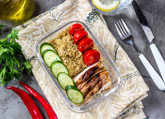 Healthy meal prep containers with quinoa, chicken and arugula