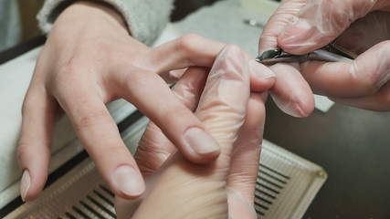Cuticle treatment is one of the stages of processing the cuticle. Woman's hands at manicure procedures.