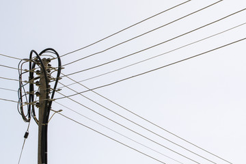 Electric pole and cables on white sky background