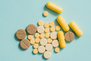 Yellow pills and capsules on a blue background.