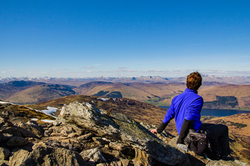A male hiker sits upright and rests and looks in to the distance on a clear bright sunny day at the view of the Scottish Highlands from summit of Ben More, Trossachs