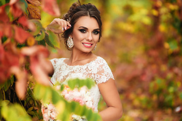 Portret of young beautiful lady in white dress. Warm autumn day