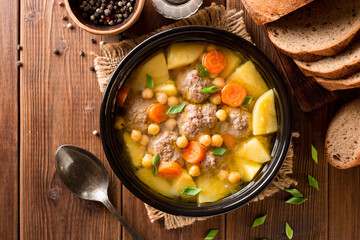 Soup with meatballs, vegetables and chickpea on wooden table