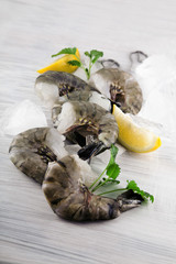fresh king prawns with lemon and lemon balm on white wooden kitchen plate can be used as background
