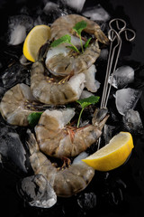 fresh raw king prawns with lemon and lemon balm on dark slate kitchen plate with napkin can be used as background