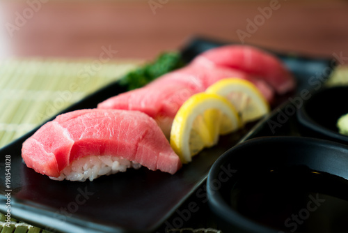 Otoro Tuna Sushi On Black Plate Along With Anese Sauce And Green Leaf Decoration