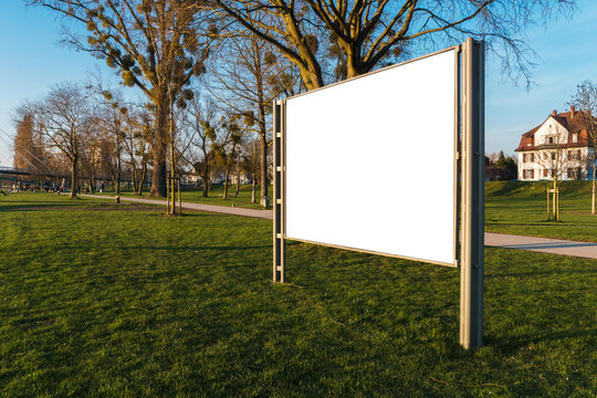 White clipped billboard in a park with the beautiful evening light - blank mockup -commercial and advertising concept