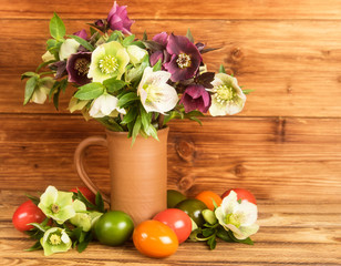 Rustic Easter still life. Easter eggs, blossoms Hellebore flowers in rustic jug.