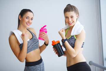 Portrait of two sporty young ladies with water bottles and towel posing in the gym.
