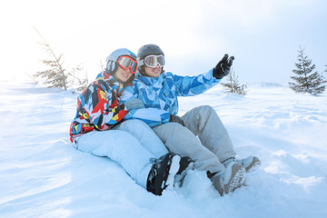 Happy couple sitting on snow at ski resort. Winter vacation