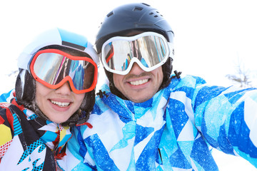 Happy couple taking selfie at ski resort. Winter vacation