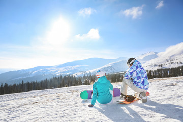 Couple of snowboarders on ski piste at snowy resort. Winter vacation