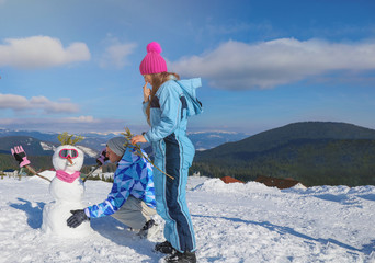 Couple making snowman at ski resort. Winter vacation