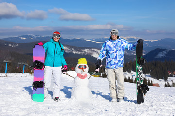 Happy couple with snowman and snowboards at ski resort. Winter vacation