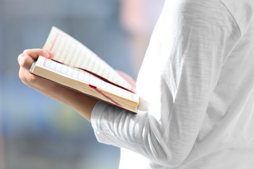 Young Muslim man reading Quran on blurred background
