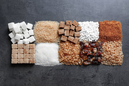 Flat lay composition with different types of sugar on gray background