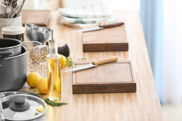 Cutting boards with kitchenware prepared for cooking classes on wooden table